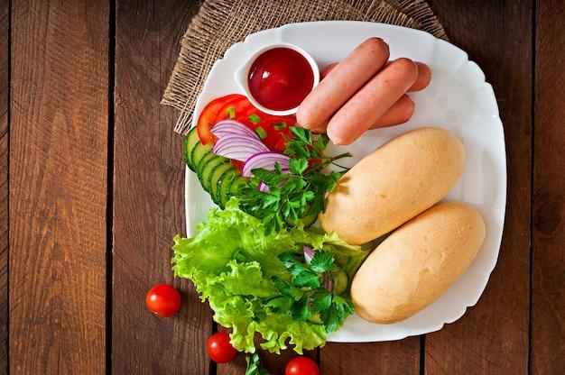 Ingrédients pour la préparation de hot-dogs sur une plaque blanche