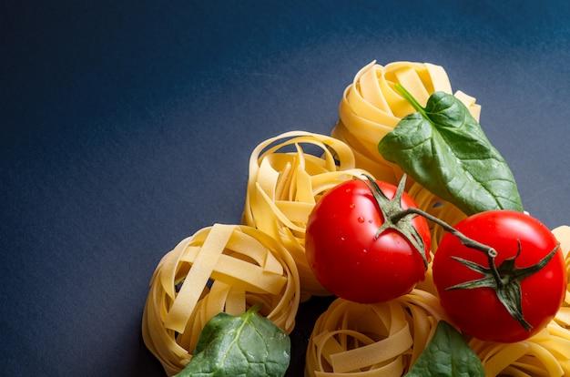 Ingrédients pour la préparation de pâtes italiennes - spaghettis, fusilli, fettuccines, tomates.
