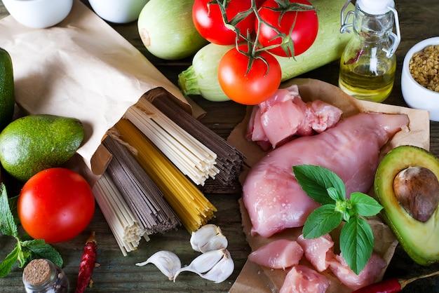 Ingrédients pour préparer des nouilles aux légumes, viande de poulet crue