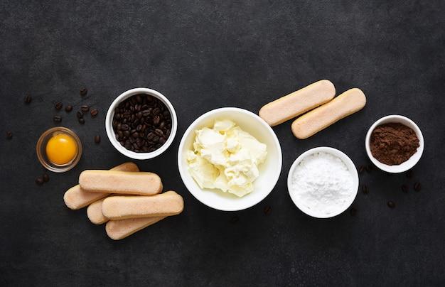 Ingrédients pour préparer le tiramisu sur fond noir. processus de cuisson. dessert italien classique.