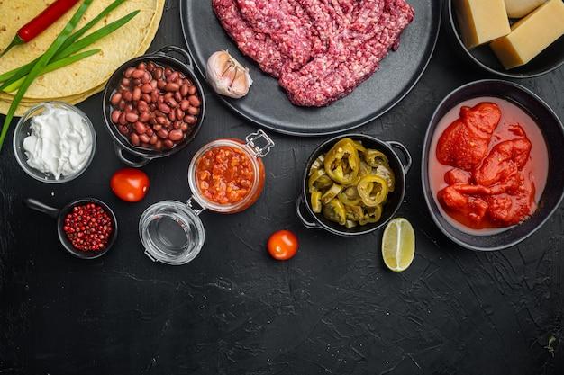 Ingrédients pour quesadilla au poulet: tortilla, maïs, poulet, oignon, tomates et poivrons, fromage, sur fond noir
