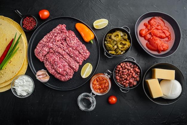 Ingrédients pour quesadilla au poulet: tortilla, maïs, poulet, oignon, tomates et poivrons, fromage, sur table noire, vue de dessus à plat