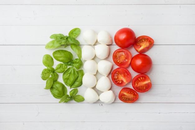 Les ingrédients pour une salade caprese. basilic, boulettes de mozzarella et tomates. drapeau italien