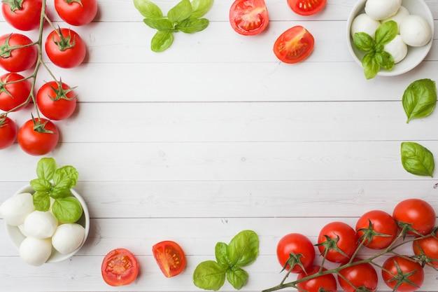 Les ingrédients pour une salade caprese. basilic, boulettes de mozzarella et tomates