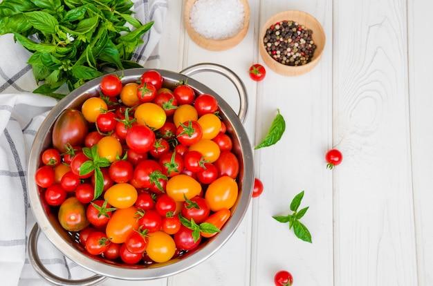 Ingrédients pour salade de légumes d'été avec tomates cerises, basilic, huile d'olive et sel sur une surface en bois blanche