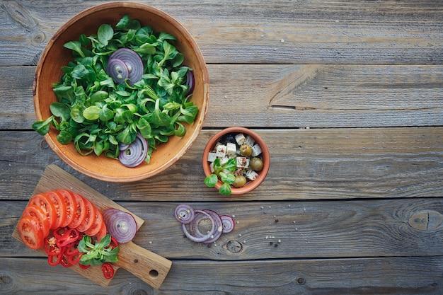 Ingrédients pour salade de légumes sur une surface en bois: feuilles de laitue, tomates, poivrons rouges, oignons, olives, huile et fromage