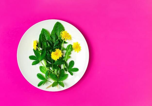 Ingrédients pour une salade verte fraîche avec des pissenlits et des fleurs comestibles sur une assiette