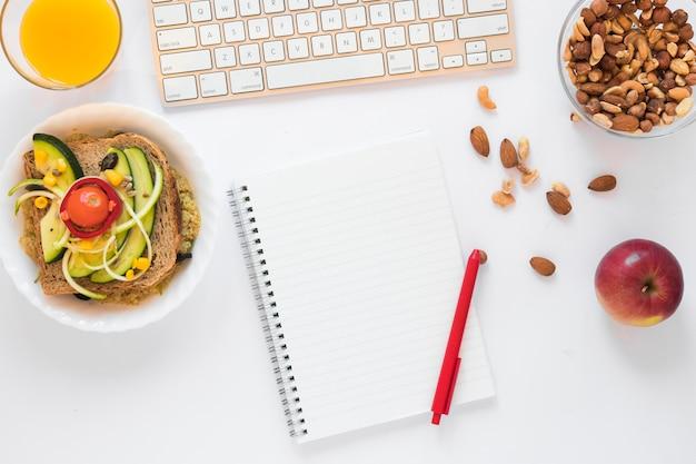 Ingrédients pour sandwich; jus; fruits secs; pomme et bloc-notes vide avec un stylo sur fond blanc