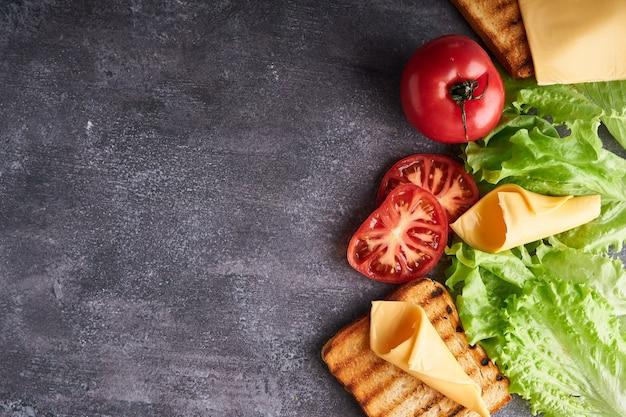 Ingrédients pour un sandwich végétarien sur une table grise espace copie vue de dessus