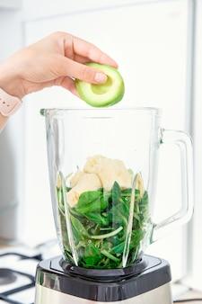 Ingrédients pour les smoothies verts de désintoxication dans un mélangeur épinards banane et avocat vue latérale la main remplit un mélangeur ou un mélangeur avec des ingrédients sains avocat et épinards