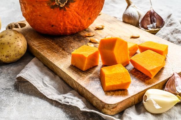 Ingrédients pour la soupe de potiron. morceaux de citrouille sur une planche à découper. soupe à la crème. cuisine végétarienne