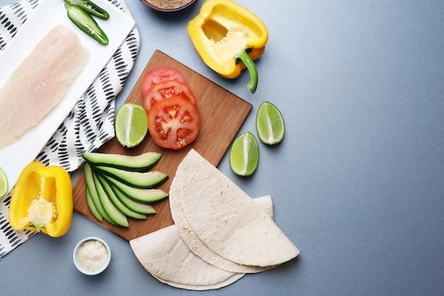 Ingrédients pour tacos au poisson sur table grise
