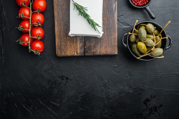 Ingrédients principaux de la salade grecque, mélange d'olives fraîches, fromage feta, tomates, sur fond noir, vue de dessus