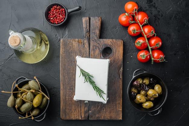 Ingrédients principaux de la salade grecque, mélange d'olives fraîches, fromage feta, tomates, sur table noire, mise à plat