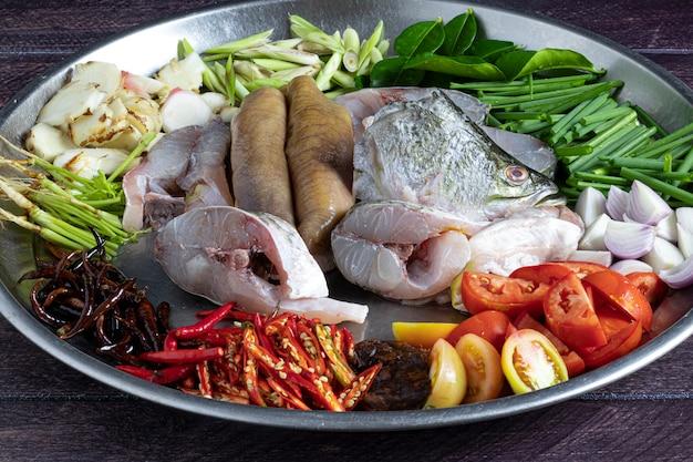 Ingrédients qui serviront à faire du tom yum avec des poissons de bar