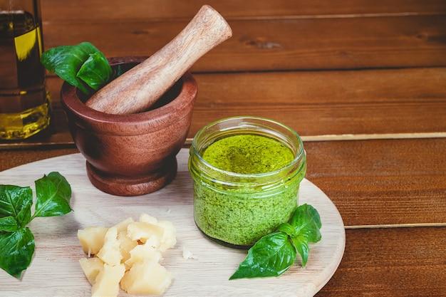 Ingrédients de la recette pesto sauce italienne. sauce pesto verte maison au basilic, pignons, ail, citron, huile d'olive et mortier de bois sur fond de table en bois
