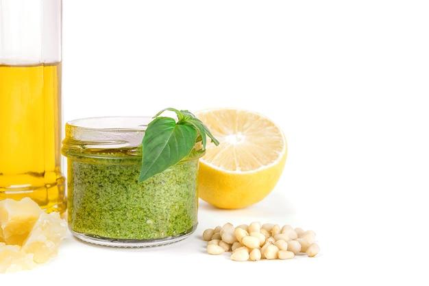 Ingrédients de la recette pesto sauce italienne. sauce pesto verte maison au basilic, pignons de pin, ail, citron, huile d'olive sur fond blanc clair.