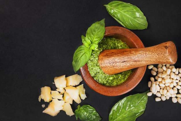 Ingrédients de la recette pesto sauce italienne. sauce pesto verte maison au basilic, pignons de pin, ail, citron, huile d'olive et mortier de bois sur fond noir foncé. vue de dessus