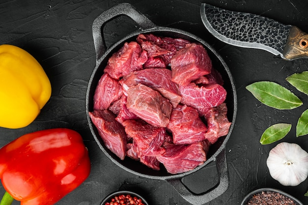 Ingrédients de recette de ragoût de boeuf cru irlandais sertie de poivron doux, dans une poêle en fonte, sur table en pierre noire, vue de dessus à plat
