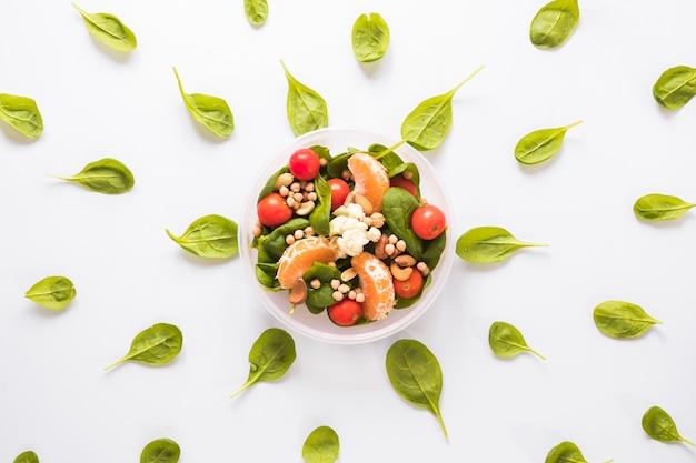 Ingrédients sains dans un bol entouré de feuilles disposées sur un fond blanc