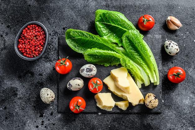 Ingrédients salade césar, laitue romaine, tomates cerises, œufs, parmesan, ail, poivre. fond noir. vue de dessus