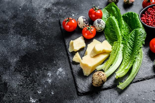 Ingrédients salade césar, laitue romaine, tomates cerises, œufs, parmesan, ail, poivre.