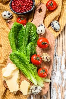 Ingrédients salade césar sur une planche à découper. laitue romaine, tomates cerises, œufs, parmesan, ail, poivre. fond blanc. vue de dessus