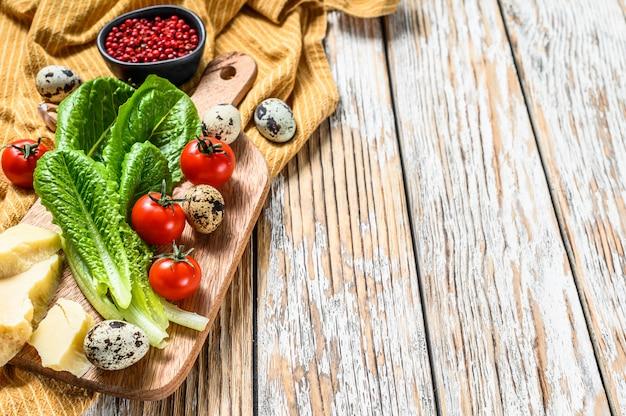 Ingrédients salade césar sur une planche à découper. laitue romaine, tomates cerises, œufs, parmesan, ail, poivre. fond blanc.
