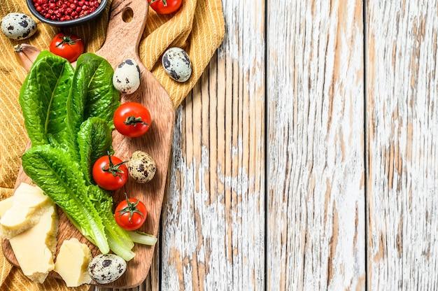 Ingrédients salade césar sur une planche à découper. laitue romaine, tomates cerises, œufs, parmesan, ail, poivre.