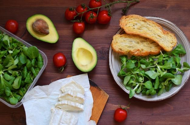 Ingrédients de la salade: fromage de chèvre, tomates, avocat et pain au bois rustique dar