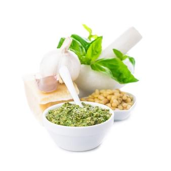 Ingrédients de la sauce pesto : basilic vert frais, parmesan, pignons de pin et ail. sur blanc