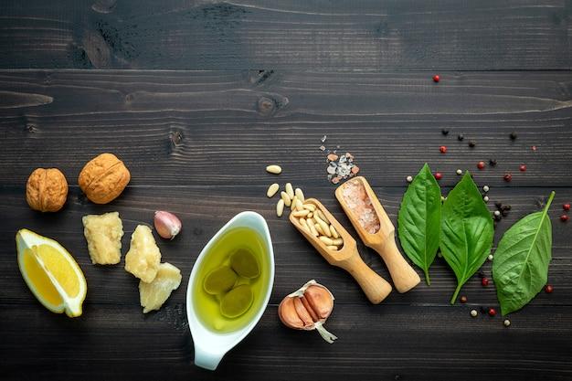 Les ingrédients de la sauce pesto verte sur un fond en bois foncé.