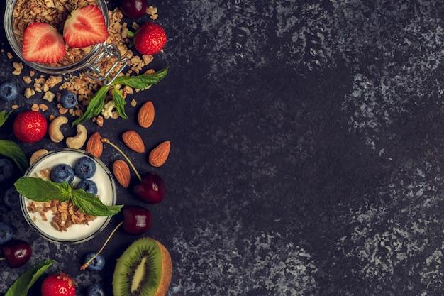 Ingrédients savoureux - granola, fruits, baies, yogourt et noix pour le petit déjeuner