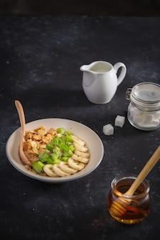 Ingrédients savoureux petit-déjeuner sain pour cuisiner avec du lait et des flocons d'avoine, banane, kiwi sur fond rose