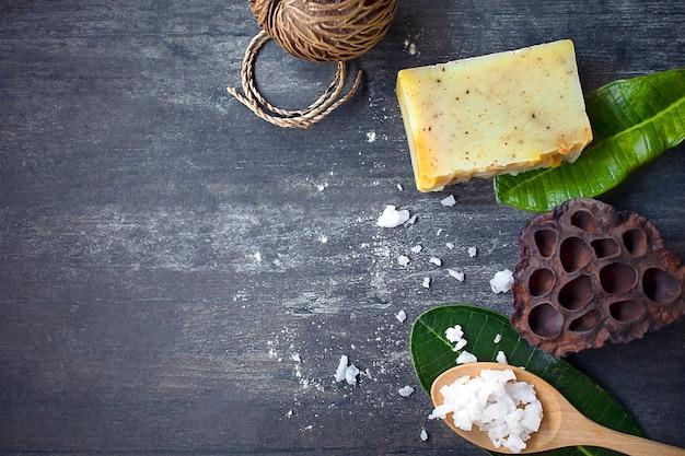 Ingrédients de spa, sel blanc, savon fait maison jaune, feuilles vertes tropicales sur bois foncé