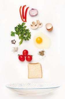 Les ingrédients tombant de l'oeuf au plat. ingrédients du petit déjeuner sain.