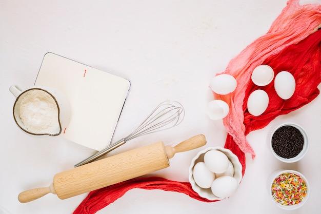 Ingrédients et ustensiles de cuisine près du cahier