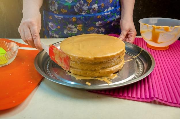 Ingrédients et ustensiles de cuisson pour la cuisson du gâteau éponge. gâteau éponge de cuisson. femme met la crème sur les gâteaux