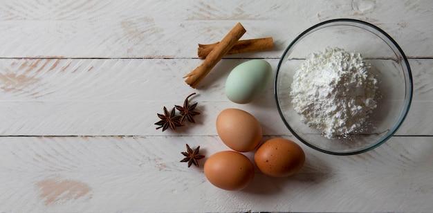 Ingrédients et ustensiles pour cuisiner sur un fond en bois