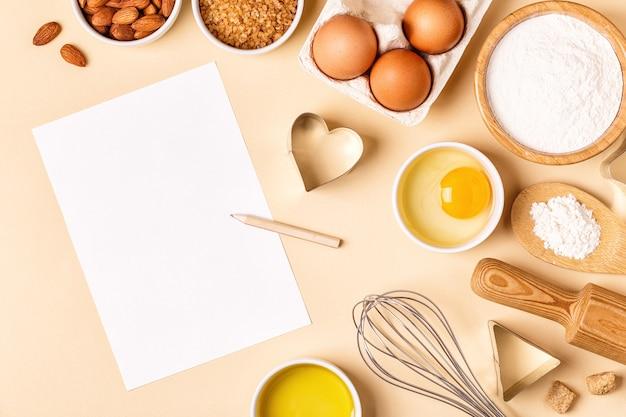 Ingrédients et ustensiles pour la cuisson sur fond pastel, vue de dessus.