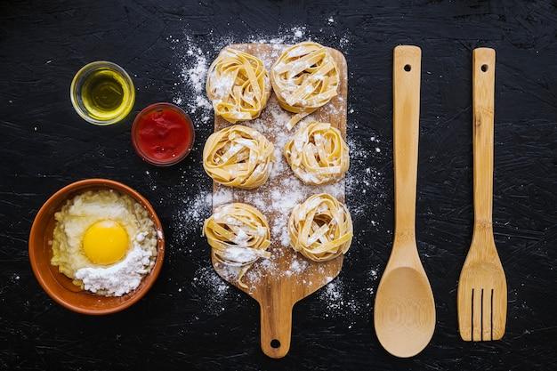 Ingrédients et ustensiles près des pâtes avec de la farine