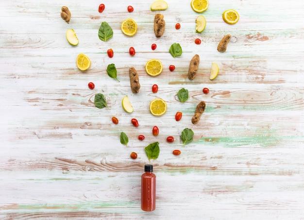 Ingrédients variés de jus mélangés faits maison placés au-dessus d'une bouteille de boissons biologiques sur fond de bois rustique. aliments et boissons sains de style de vie, concept de régime.