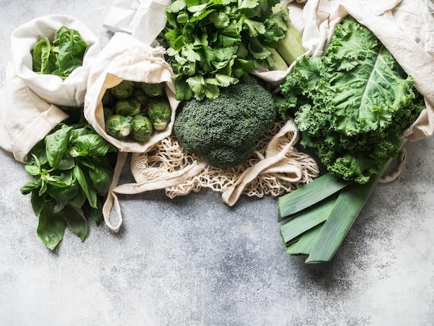 Ingrédients végétaliens sains et verts pour la cuisine. divers légumes verts et herbes propres dans des sacs en textile. produits du marché sans plastique. concept zéro déchet à plat.