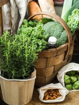 Ingrédients végétariens sains pour la cuisine. divers légumes propres, herbes, noix et pain dans un panier sur une chaise en bois. produits du marché sans plastique.