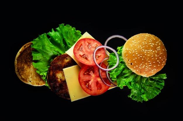 Ingrédients volants pour un hamburger fait maison sur fond noir.