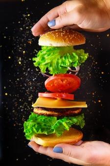 Ingrédients volants pour un hamburger fait maison sur fond noir