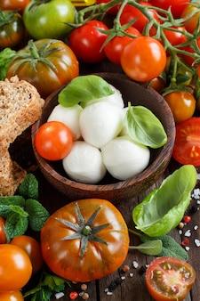 Ingridients italiens pour salade caprese sur surface en bois