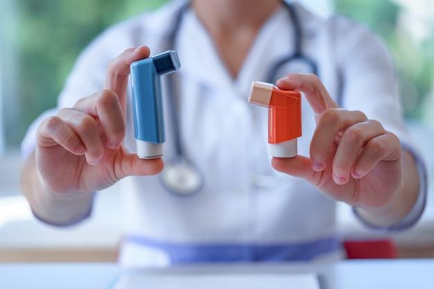 Inhalateurs pour l'asthme dans les mains du médecin pour un patient asthmatique pendant une consultation médicale et un examen