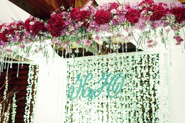 Les initiales des nouveaux mariés se tiennent devant les guirlandes lumineuses