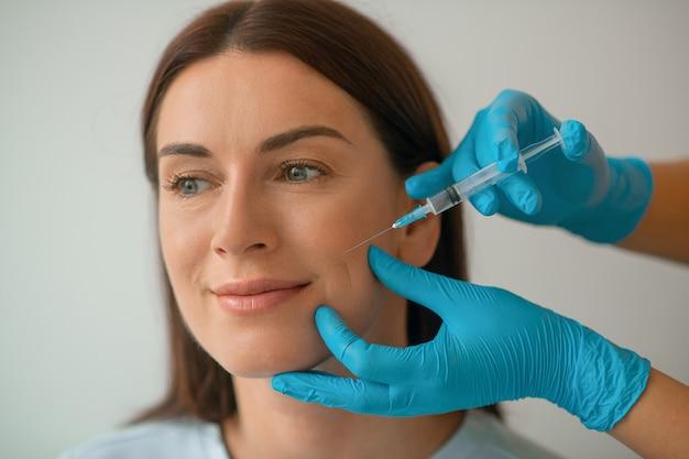 Injections de collagène. cosmétologue injectant du collagène au visage de ses clients